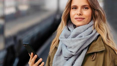 Kundin mit Smartphone steht am Bahnsteig