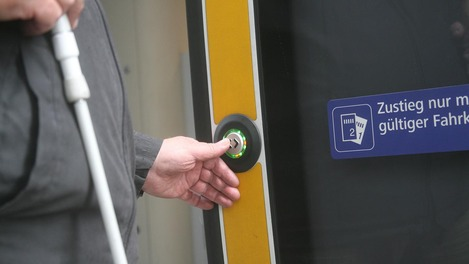 Passenger presses button for barrier-free entry