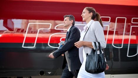 Businessreisende vor einem ÖBB Railjet