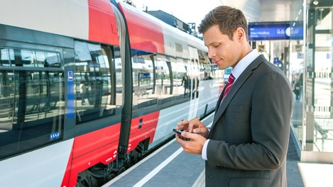 Businessreisender am Bahnsteig vor ÖBB Talent