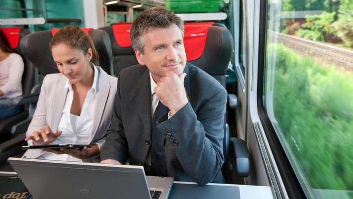 Business travelers in the ÖBB Railjet with laptop and tablet
