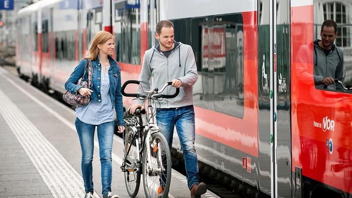 Paar am Bahnsteig mit Fahrrädern