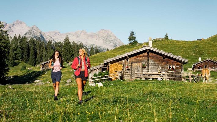 Zwei Frauen wandern über einen Hügel bei Dämmerung