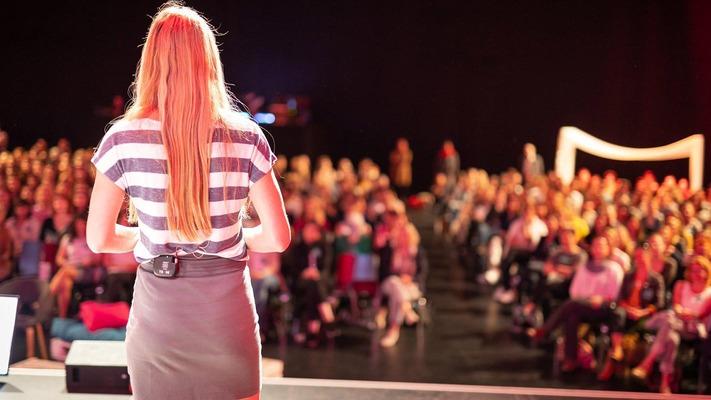 Frau steht auf Bühne vor Publikum