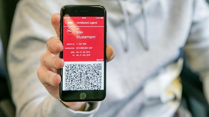 Jugendlicher mit Handy zeigt seine Vorteilscard in der ÖBB App
