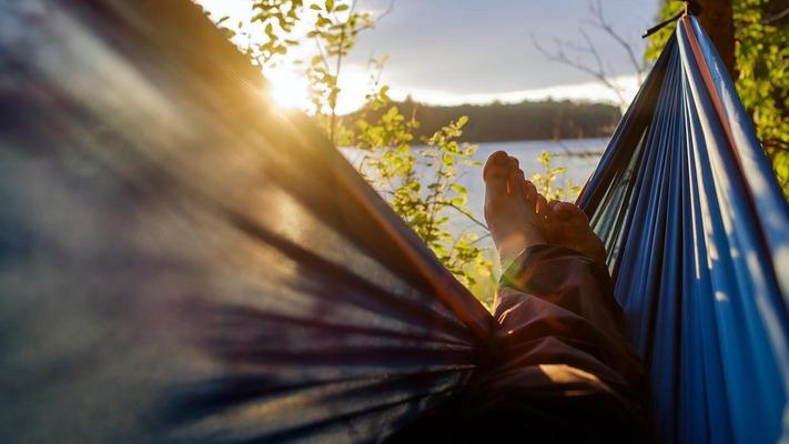 Person liegt in Hängematte und blickt Richtung Sonnenuntergang